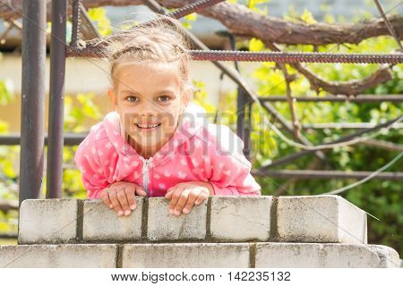 Seven Years' Happy Girl Hanging On A Brick Fence And Looked In The Frame
