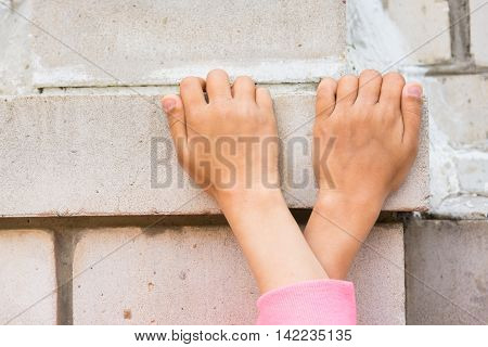 Crossed Children's Hands Seized On The Brick Wall