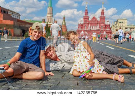 Grandfather with grandson and granddaughter sit on red square