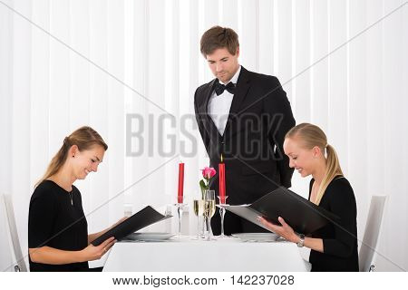 Young Happy Female Friends Looking At Menu In Restaurant With Glass Of Wine On Table