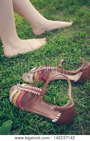 Bare female legs on grass near stand sandals. Selective focus tinted