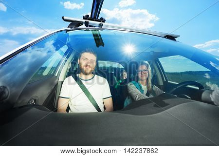 Happy young family during car trip on sunny day, view through windscreen shot with wide lens