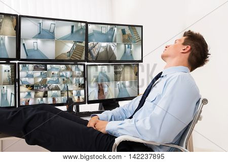 Security Guard Sleeping In Front Of Multiple Computers Showing CCTV Footage