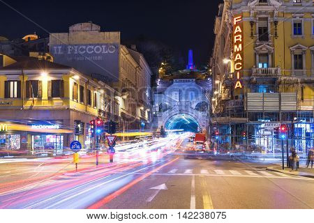 Trieste, Friuli Venezia Giulia region - March 2015, Italy: Night view of the city of Trieste with car traffic lights trails Pharmacy store and McDonalds building on Piazza Carlo Goldoni.