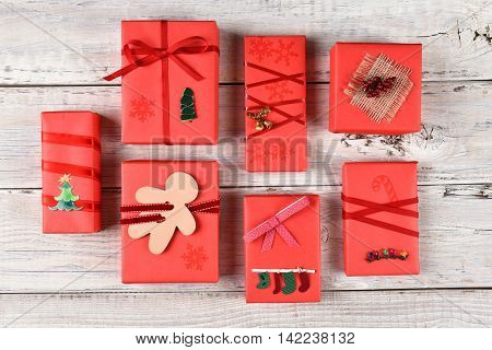 High angle view of a variety of red wrapped Christmas presents on a rustic white wood surface.