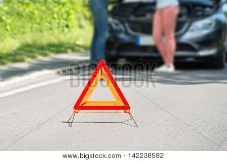 Close-up Of A Triangular Warning Sign With Couple Standing In Front Of Broken Down Car