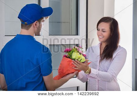 Smiling Young Woman Receiving Bouquet Of Flowers From Delivery Man At Home
