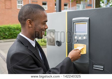 Happy Young Businessman Inserting Ticket Into Parking Machine To Pay For Parking