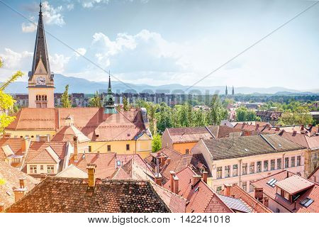 Ljubljana cityscape with saint James's Parish church and mountains on the background