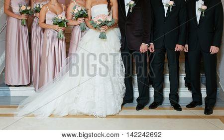 Row of bridesmaids and groomsmen at big wedding ceremony.