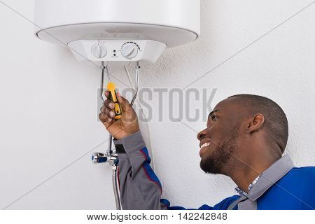 Happy Young African Male Worker Fixing Electric Boiler With Screwdriver