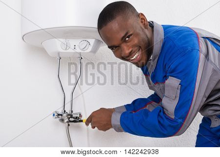 Happy Young African Male Worker Repairing Electric Boiler With Wrench