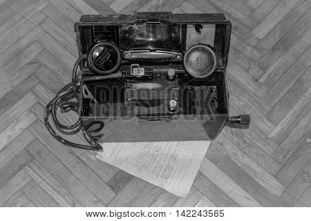 An old phone on wooden background black & white