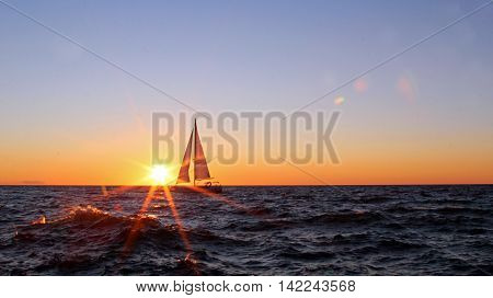 A sailboat at sunset with sunflare and waves with copy space