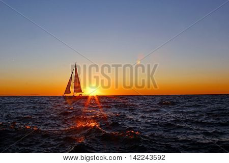 A sailboat at sunset with sunflare and waves