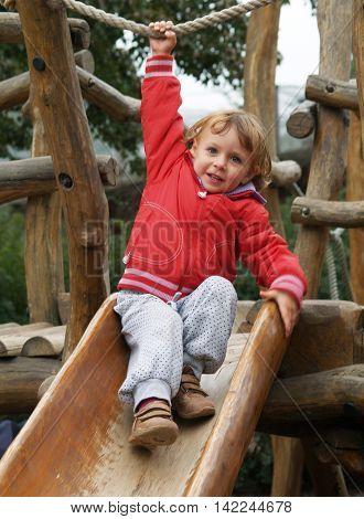 Little girl in red sweatshirt playing on wooden slipway