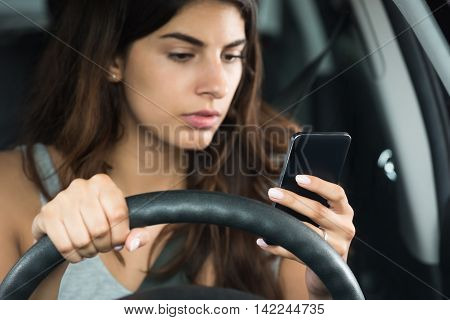 Young Woman Looking At Her Mobile Phone While Sitting Inside Car