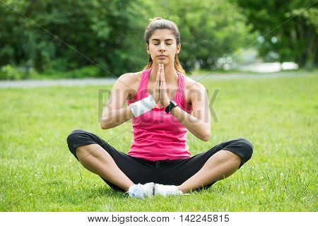 Young Woman Sitting On Grass Doing Meditation In Park