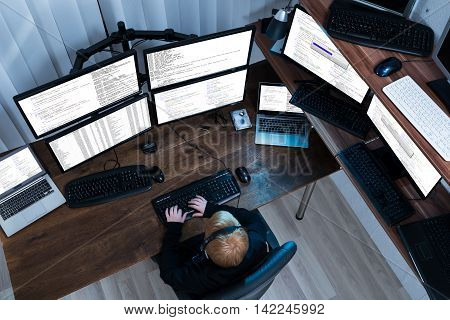 High Angle View Of A Boy Working On Multiple Computers