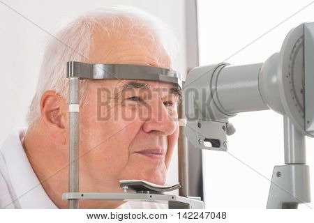 Close-up Of Senior Man Checking Eyesight In Clinic