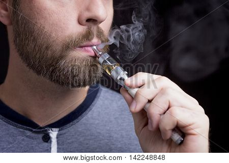 A smoking electric cigarettes on the black background