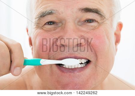 Senior Man Brushing His Teeth With Toothbrush