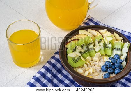 Oatmeal with kiwi, apples and blueberries. Amended orange juice in a glass and a jug. A healthy breakfast on a light table with blue checkered tablecloth