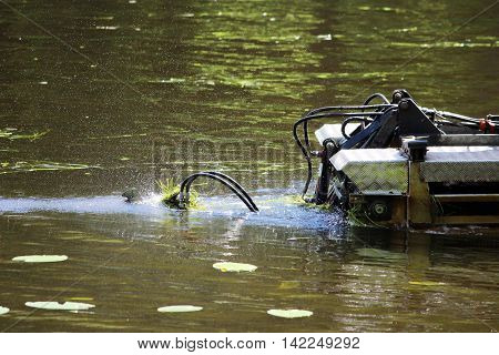 mini dredger is clearing lake algae summer day
