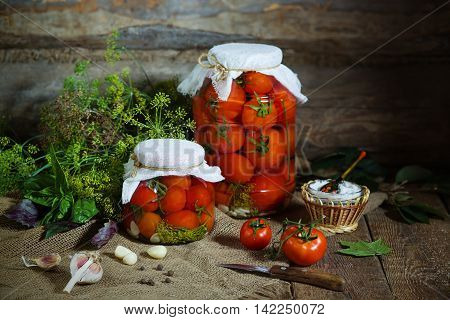 A few jars with canning tomatoes and ingredients for conservation. Rusic style