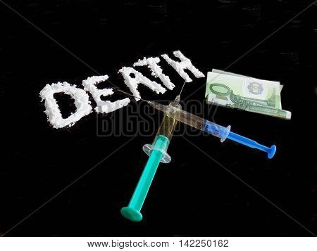 Cocaine drug powder in shaped death word, two crossed injections and hundred euro banknote on black background