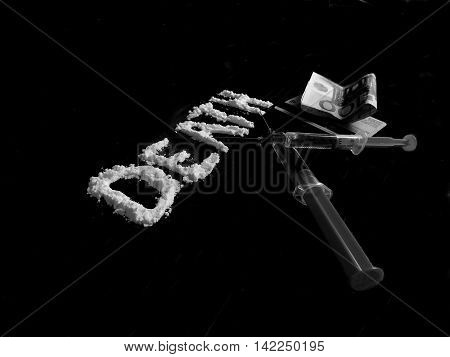 Cocaine drug powder in shaped death word, two crossed injections, credit card and hundred euro banknote on black background in black and white colors
