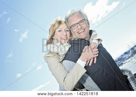 A Portrait of happy senior couple in winter season with sky on the back