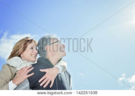A Portrait of happy senior couple in winter season with sky on the back.