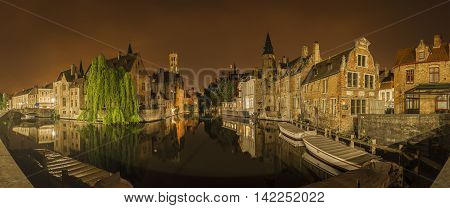 Panoramic nocturnal and iconic view of historic medieval buildings along a canal from the Rozenhoedkaai in Bruges Belgium. Buildings trees and boats are reflected in the water