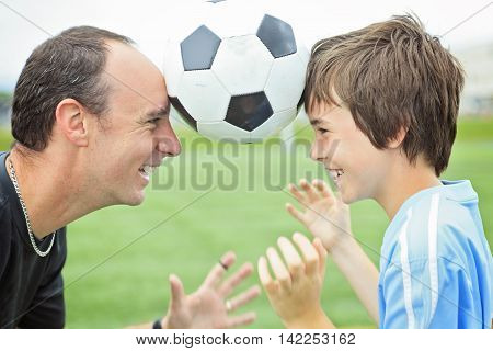 A young soccer player with is father with ball on the forehead
