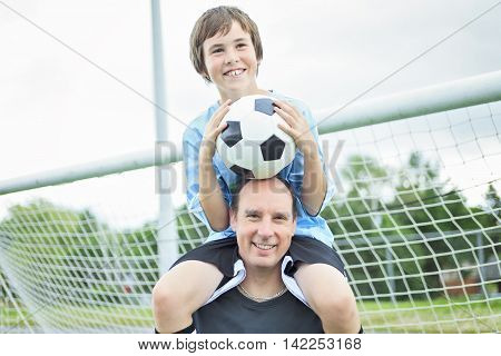 A young soccer player with his father. The boy is on the father shoulder.