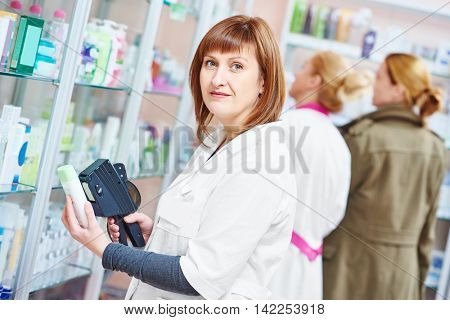 Pharmacist using labeling gun in pharmacy drugstore