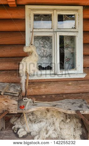 Distaff with a sheep's wool near the old house window