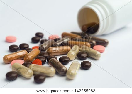 Different pills and capsules scattered on a white background. Plastic jar.