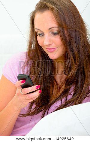 Sonriente mujer hermosa escribir texto mensajes en su teléfono móvil