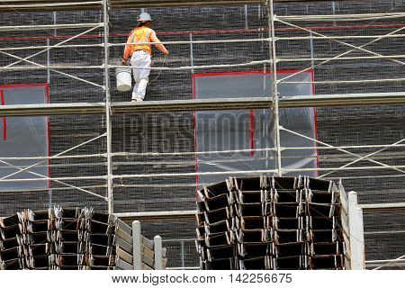 Construction worker wearing hardhat and orange safety vest holding white bucket on scaffolding at construction site with steel beams in foreground.