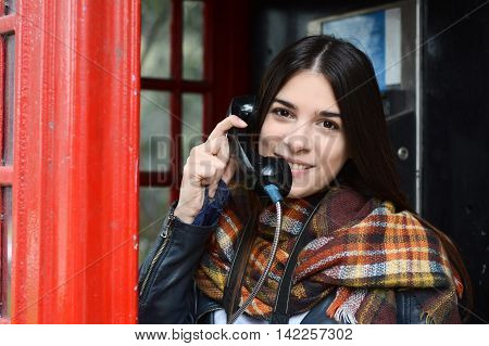 Portrait of young beautiful woman talking on phone in red box telephone. Tourism concept. Outdoors.