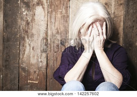 A depressed senior person with wood background