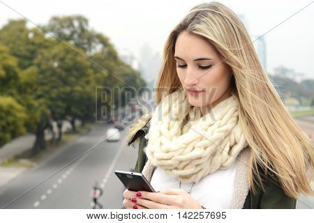Portrait of a young beautiful woman sending messages with her smartphone. Outdoors. Urban scene.