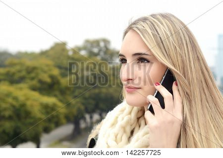 Portrait of a young beautiful woman talking on the phone. Outdoors.