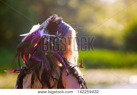 woman with war bonnet. the girl wears a homemade Indian headdress of feathers. roach, war bonnet. woman looked away. the concept of woman on the warpath