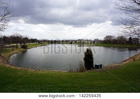 A small, man-made lake in the Wesmere Country Club subdivision of Joliet, Illinois during the Spring.
