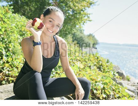 A happy sport woman with an apple on her hand on the sea border.
