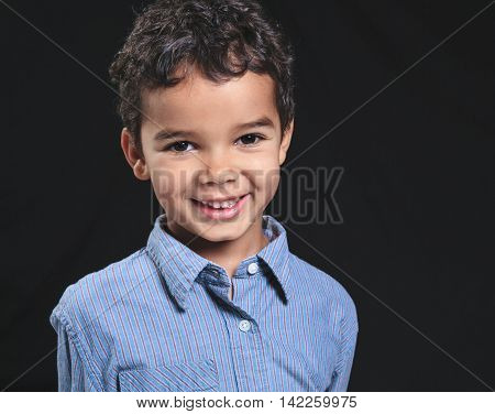 Portrait of a cute african american little boy, isolated on black background