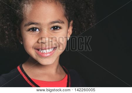 Portrait of a cute african american little girl, isolated on black background